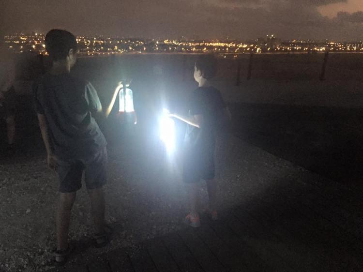 מחזיקים עששיות על רקע אורות גוש דן